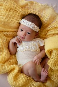 baby girl dressed in yellow vintage newborn outfit