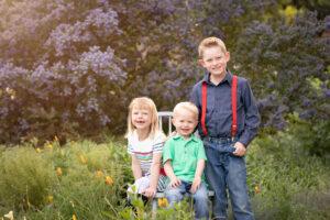 3 kids smiling in flower garden