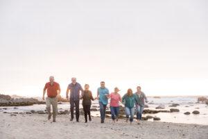 exstended family running on beach at sunset