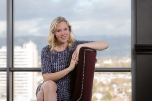 Seated business headshot with San Jose cityscape