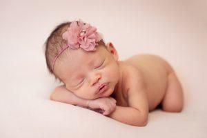 naked newborn baby girl on pink