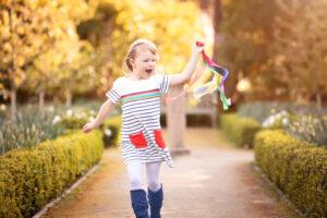 litte girl running flying rainbow of streamers